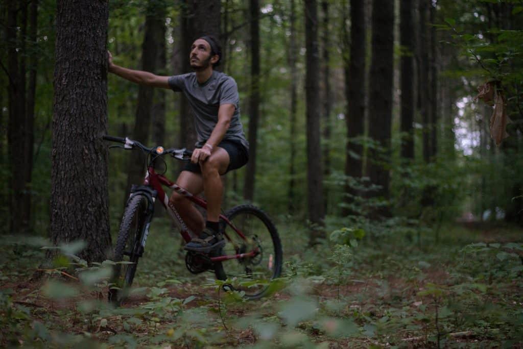 Man resting on bike in woods