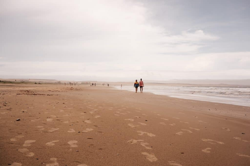 two men stroll on the beach