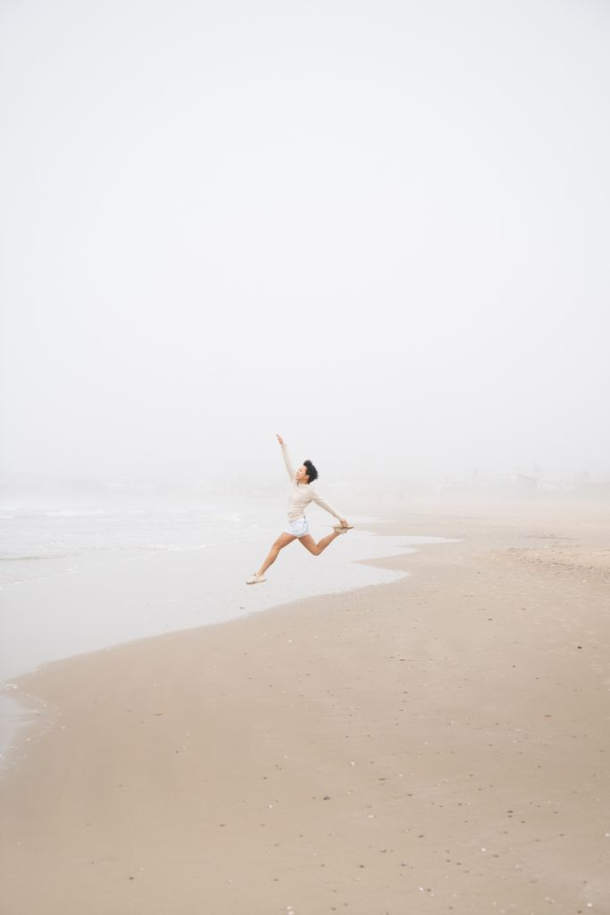 Girl jumps into air on the beach