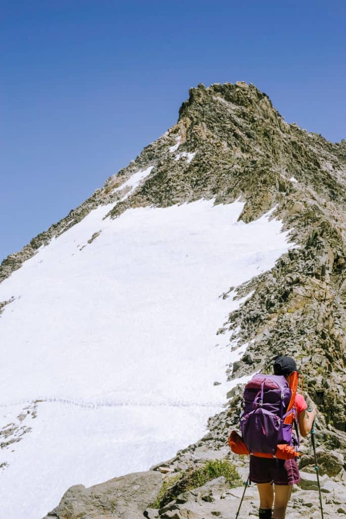 Female hiker looks into snow covered mountain path