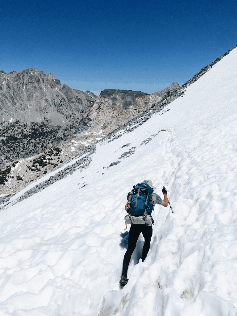 Man uses trekking poles to cross glen pass snow