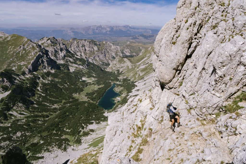 Man ascends the vertical face of Bobotov Kuk by using a cable