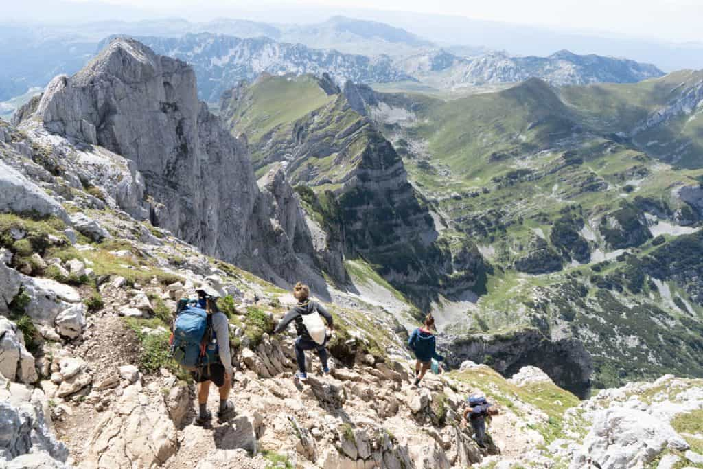 Group of people walk down steep path from Bobotov Kuk