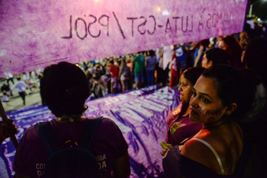Protestor looks into crowd with a banner protesting Brazil's abortion bill
