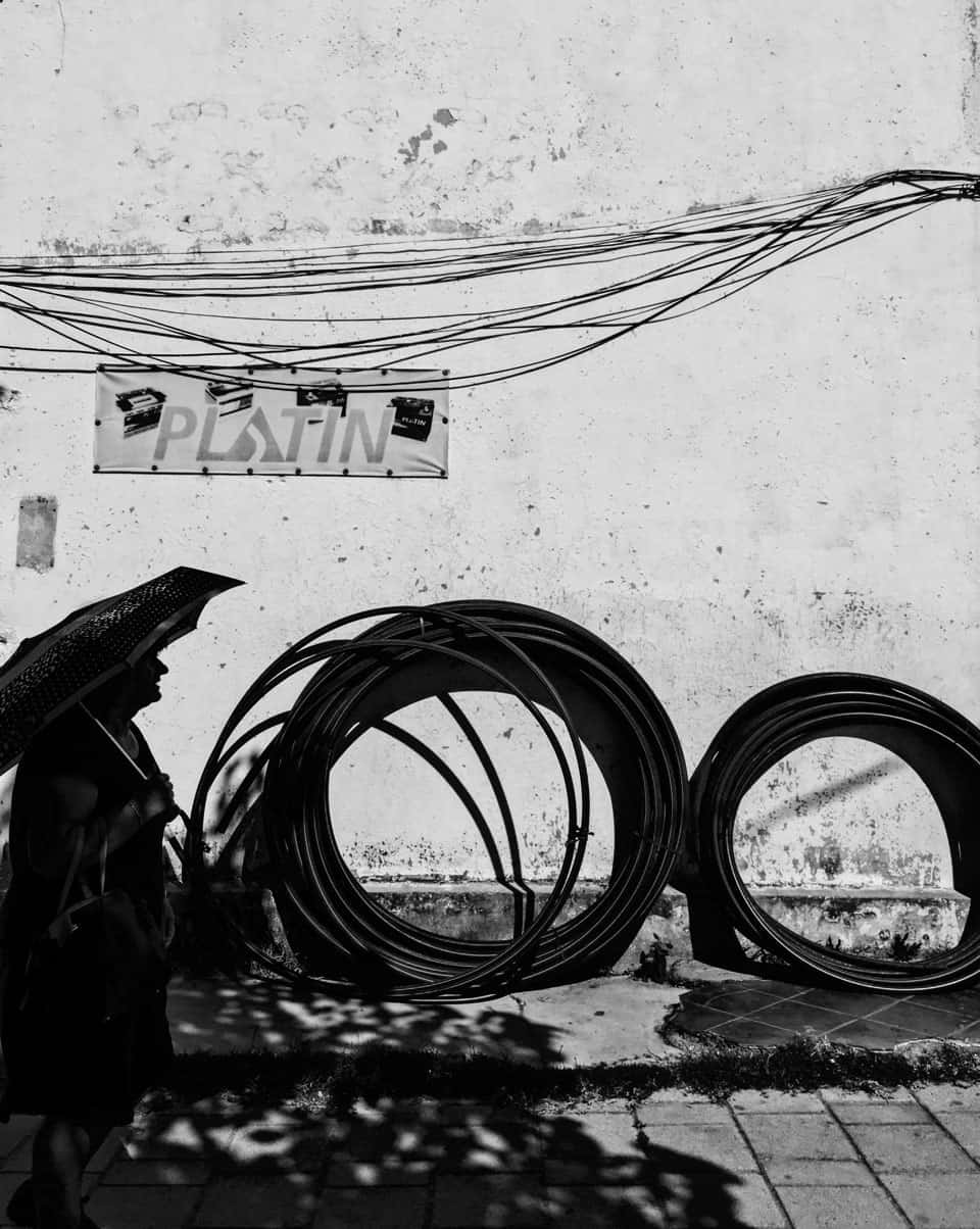 Silhouette of woman walking with huge circular bundles of wires in backdrop