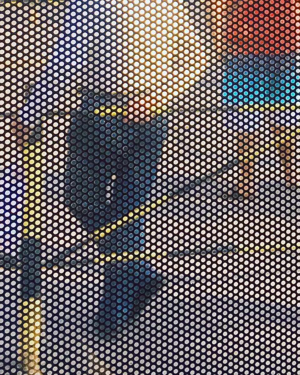 Dotted pixels construct an image of a pan standing against a fence