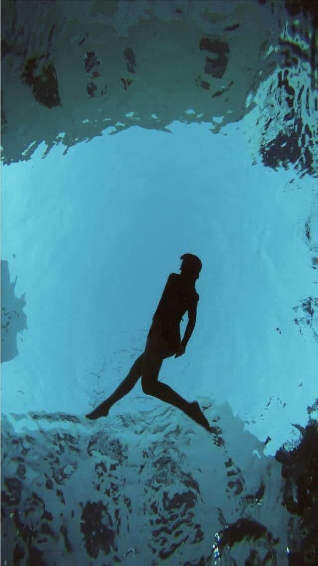 Silhouette of a woman floating in water in what appears to be a void