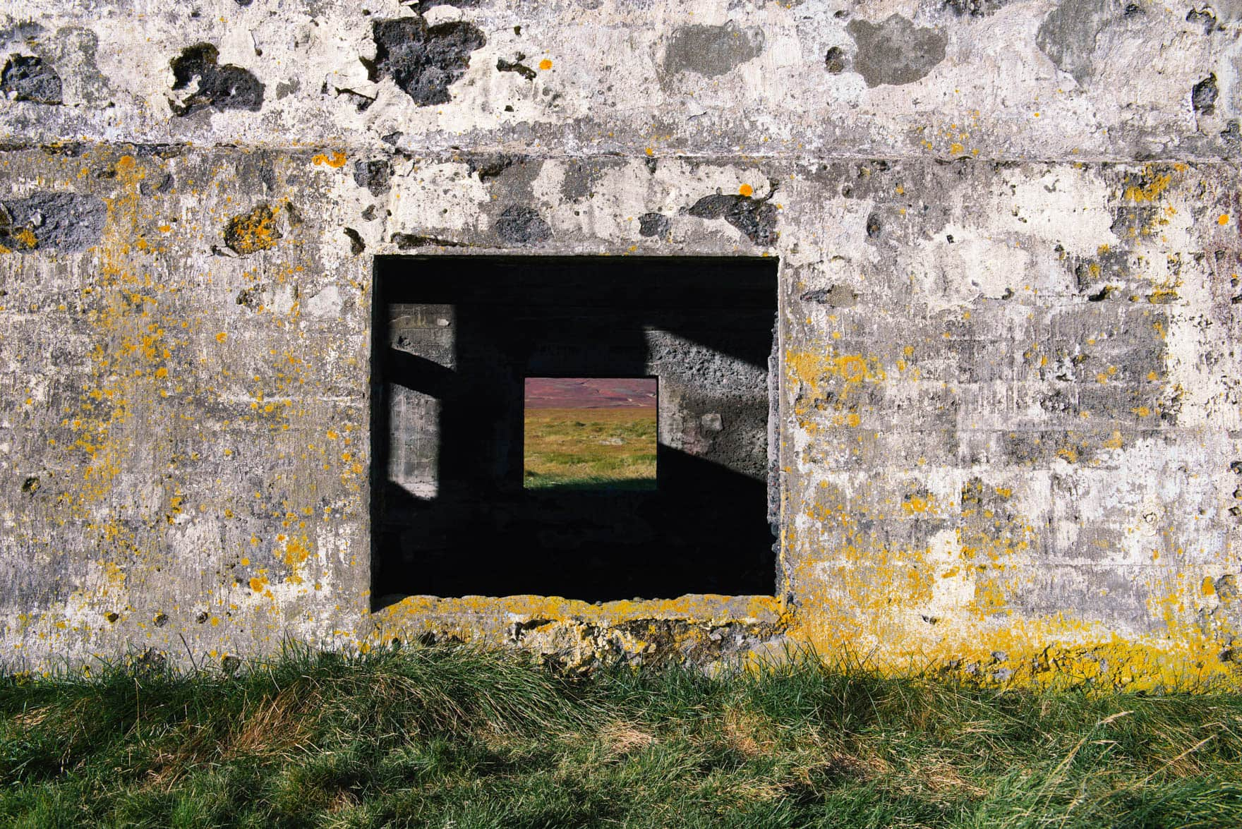 View of an open window that looks in through an abandoned concrete house and into the other window that reveals the colorful landscape on the other side
