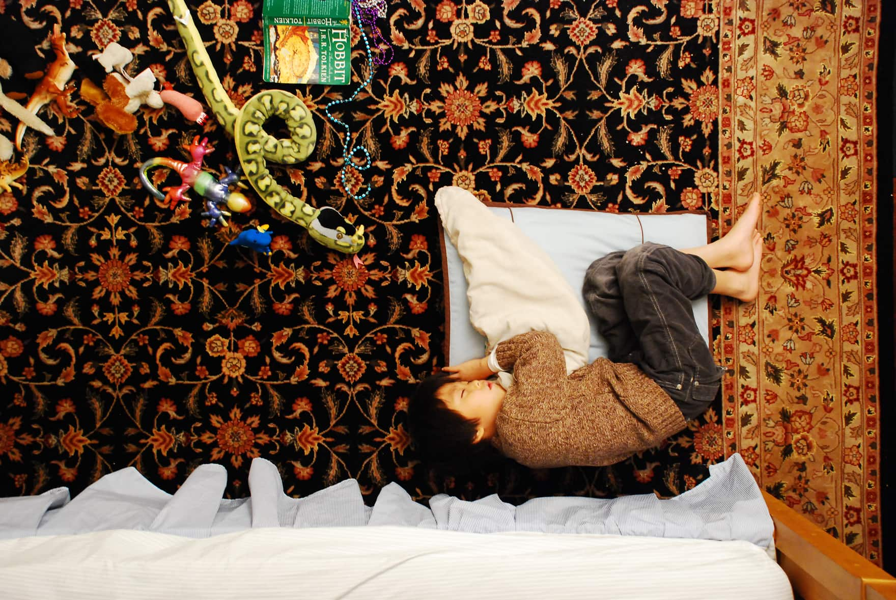 Child sleeps cuddled on a pillow on a carpeted floor while his toys are moving towards him