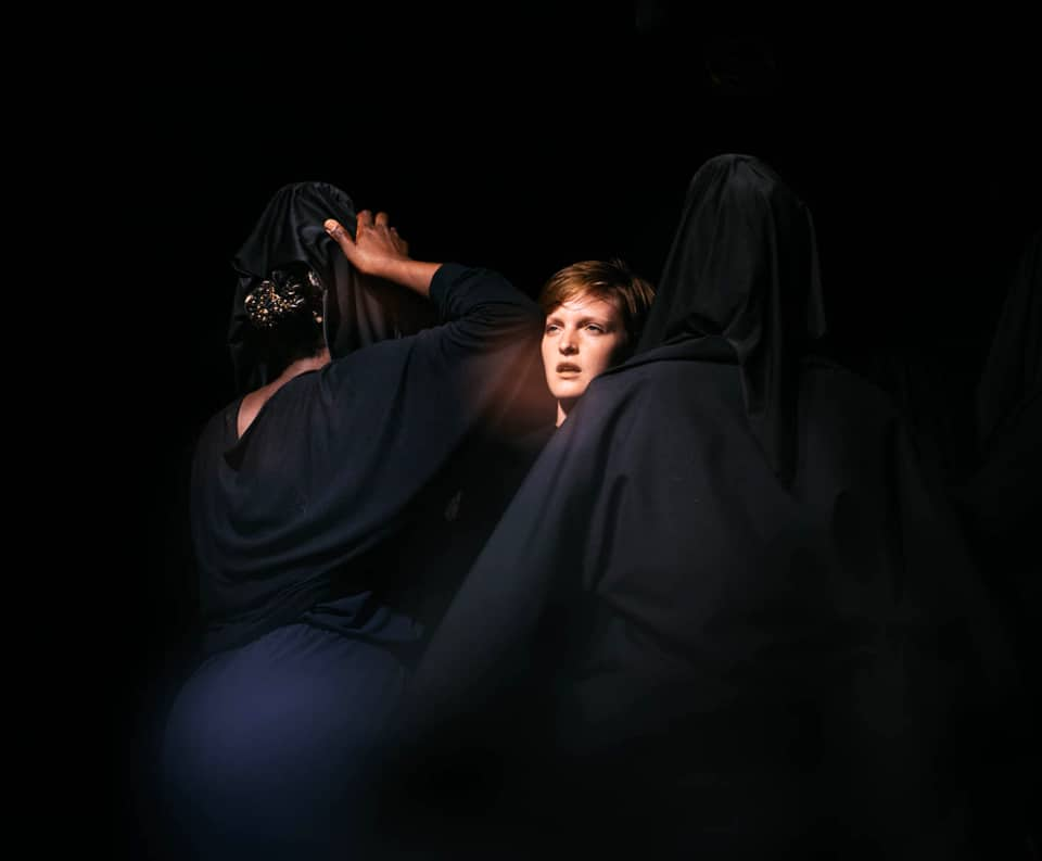 3 women huddled together one with their face visible the others shrouded in dark clothing