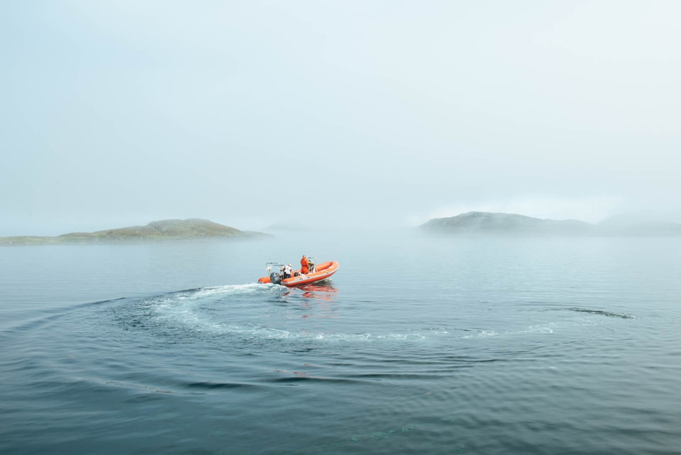 Man in a orange boat whips around in the misty sea