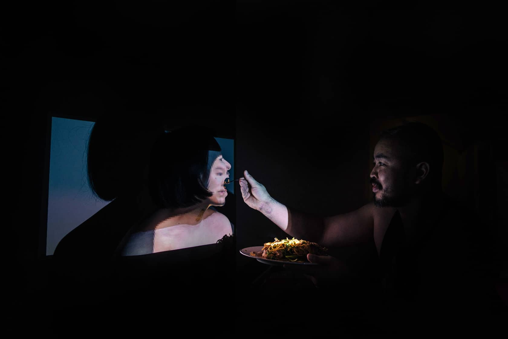 A person feed pasta to another person who is illuminated by a box