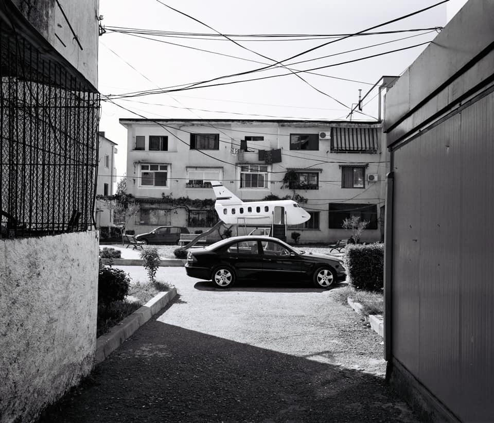 A view of a playground play with a car in the foreground shot through an alleyway
