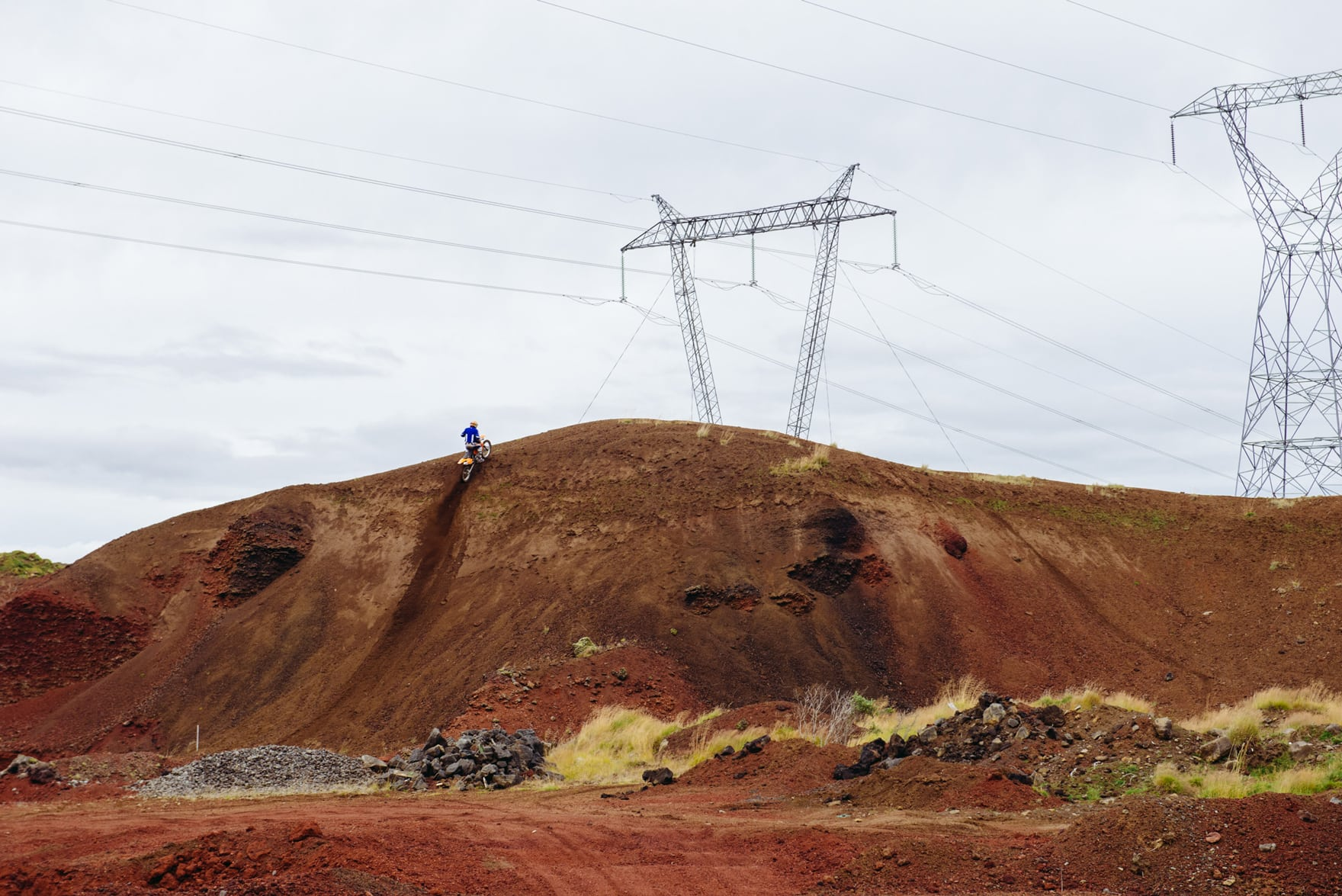 Solo Dirt bike cyclist rides up a tall red canyon with powerlines in the background