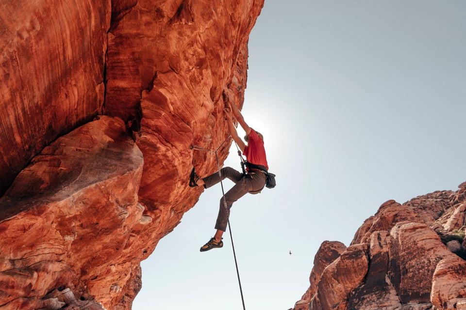 Upward shot of a man climbing in red rocks