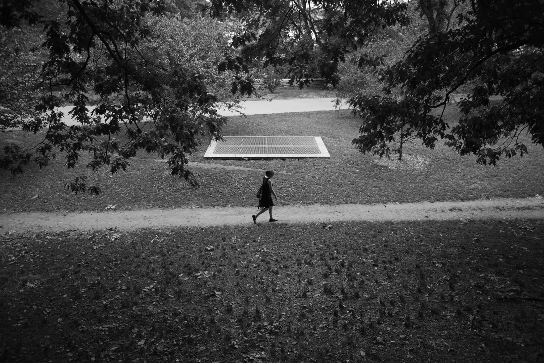 A solo woman walks on a path in Riverside Drive park in the background there is a underground vent