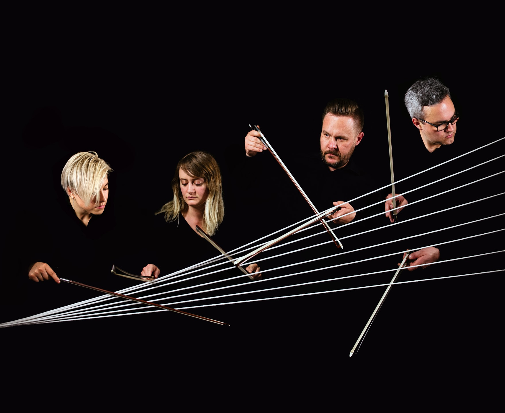 4 members of Spektral Quartet hold up their bows against lines that form a spectrum