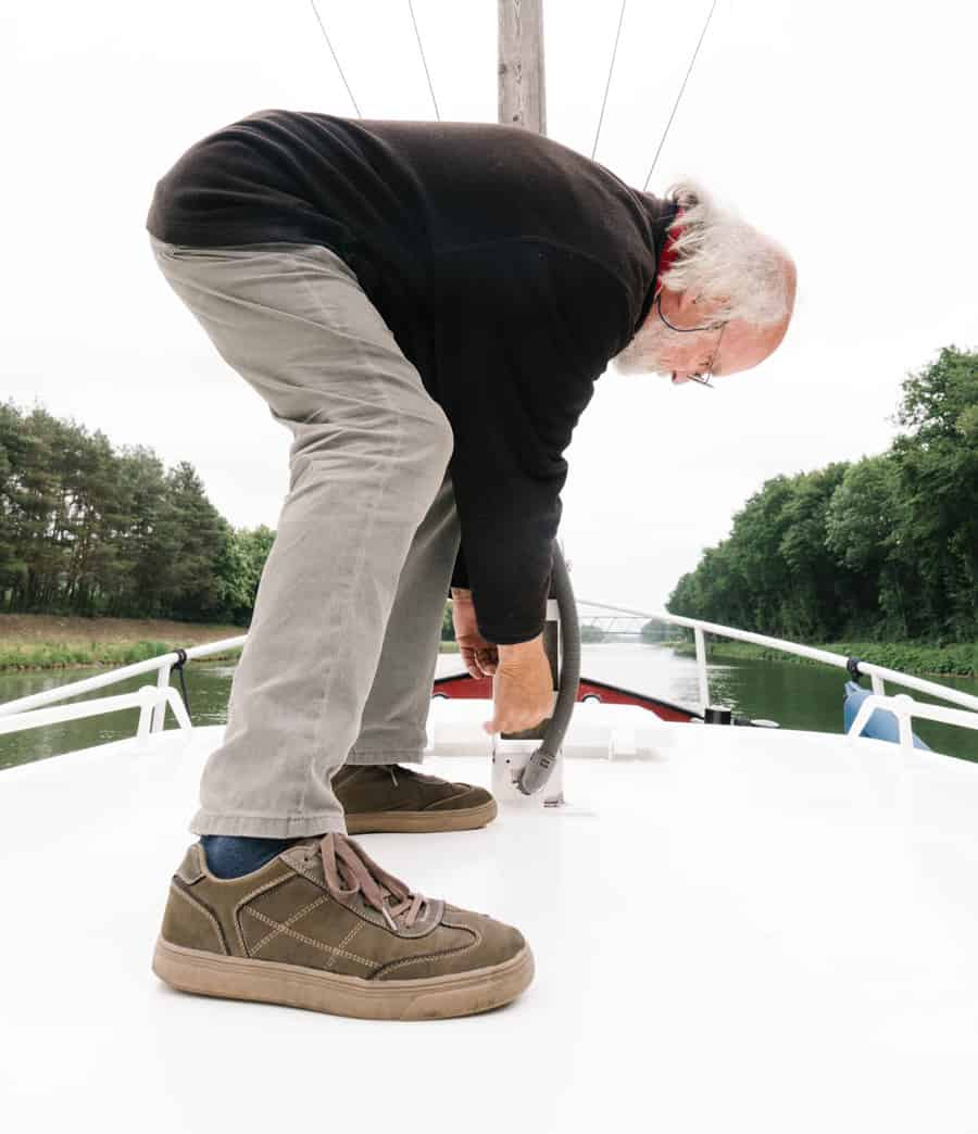 Upwards shot of a man on the deck of his boat adjusting a part