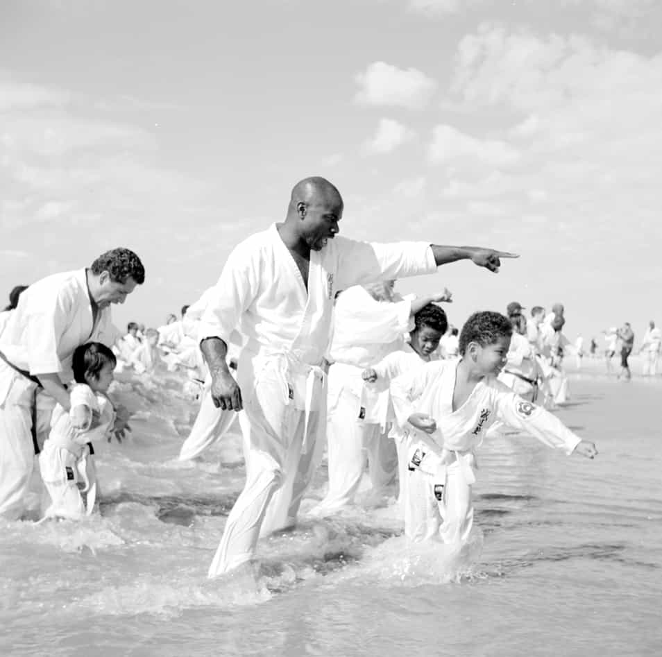 Karate teachers instruct their young students in the receding waves of Coney Island's beach