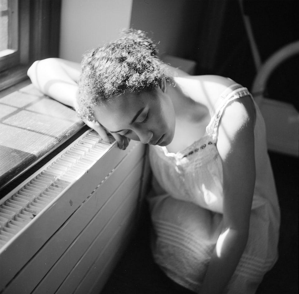 Portrait of woman resting her head near the window