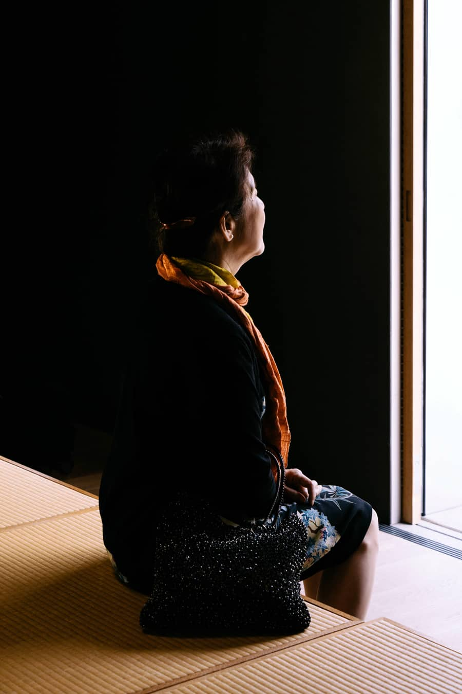 Seated woman serenely looks into the light of an open doorway